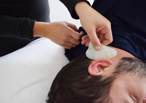Gua sha being performed on a person's neck